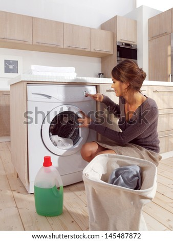 Young woman loading the washing machine in room - stock photo