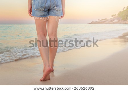 young woman long legs walking on the beach at twilight - stock photo