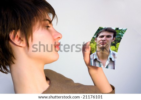 young woman looking at a picture of a man - stock photo