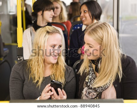 Young woman looking at cellphone while going by the bus