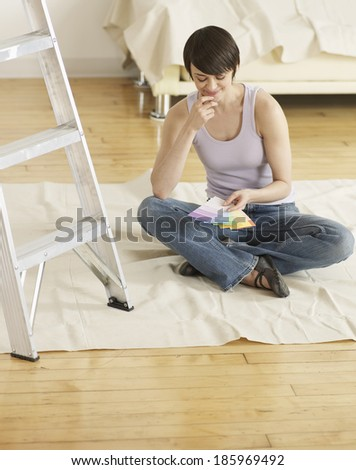 Young Woman Looking at Color Swatches on Floor