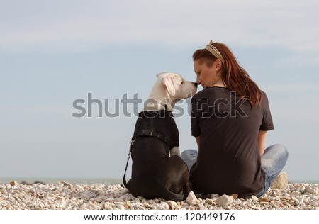 Young woman looking at dog nose to nose - stock photo
