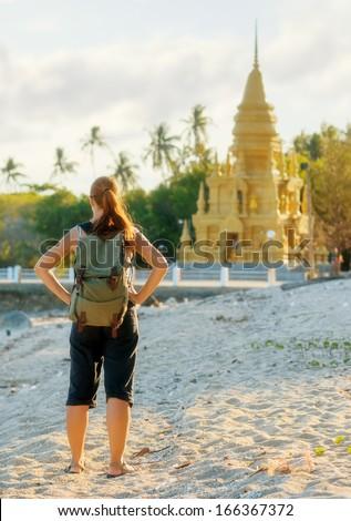 Young woman looking at golden pagoda. Hiking at Asia. - stock photo