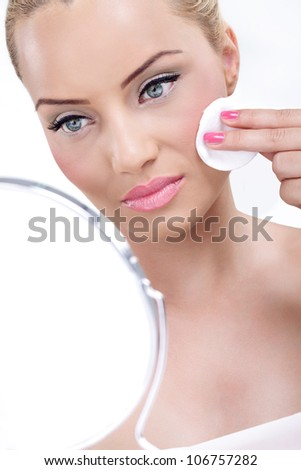 Young woman looking at her complexion in the mirror  and cleaning her skin with cotton pad - stock photo