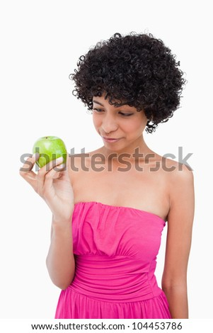 Young woman looking at her delicious green apple held by her right hand - stock photo