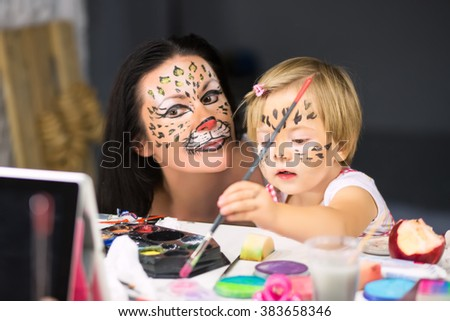Young woman looking at little girl painting in front of the mirror - stock photo