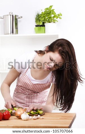 young woman looking at the paprika she is chopping for salad - stock photo
