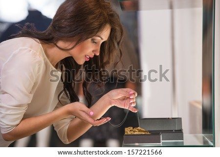 Young woman looking at the shop showcase and taking jewelry to look at it closer - stock photo
