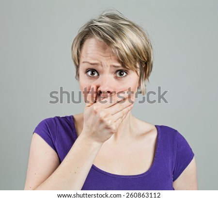 Young woman looking disturbed by something, isolated on white - stock photo