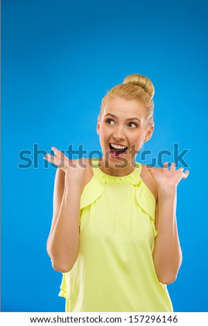 Young woman looking excited against blue background.
