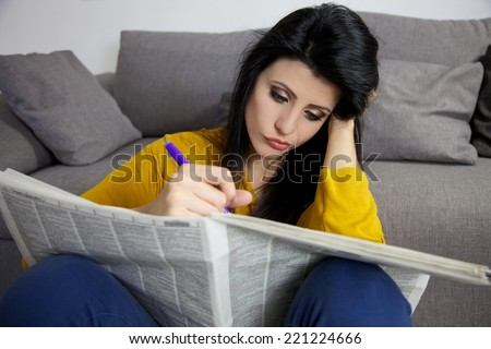 young woman looking for a job on newspaper with no success - stock photo