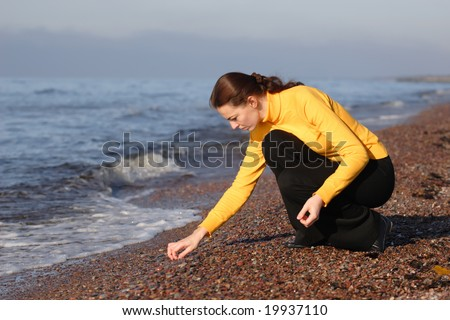 Young woman looking for an amber on a seaside