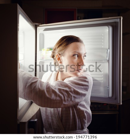Young woman looking for some snack in fridge late at night. - stock photo