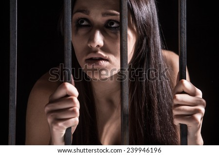 Young woman looking from behind bars. trapped woman behind iron bars  - stock photo