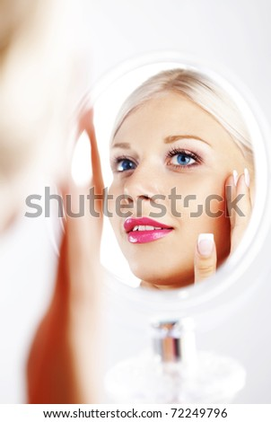 Young woman looking in cosmetic mirror - stock photo