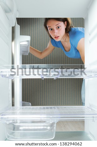 Young woman looking in his empty fridge - stock photo