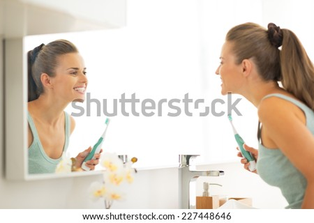 Young woman looking in mirror after brushing teeth - stock photo
