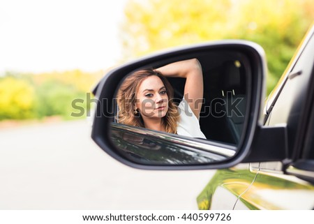 Young woman looking in the car mirror