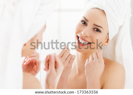 Young woman looking in the mirror and smiling, using dental floss to clean her teeth  - stock photo