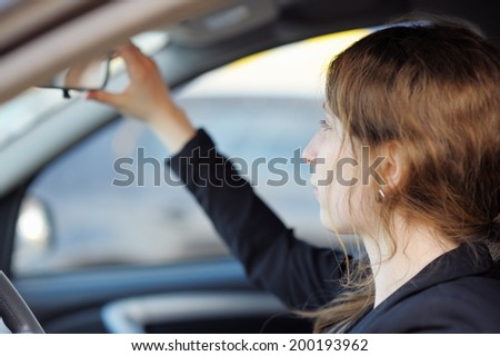 Young woman looking in the mirror in a car
