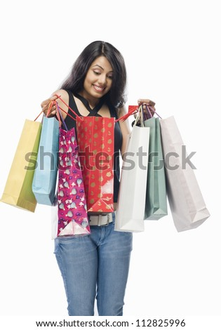Young woman looking into a shopping bag - stock photo