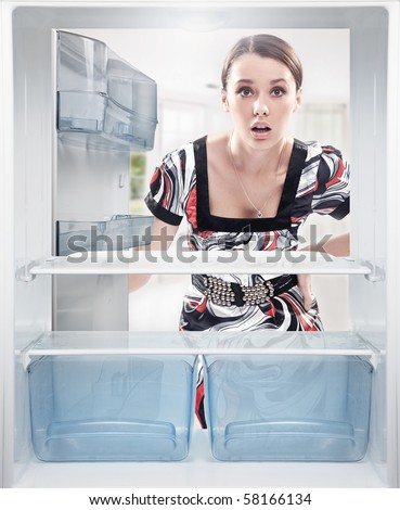 Young woman looking on empty shelf in fridge. - stock photo