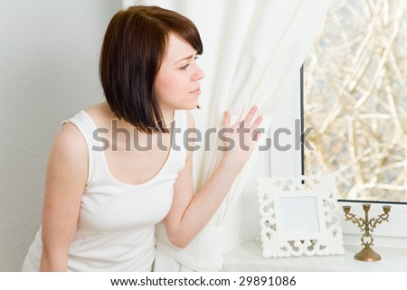 Young woman looking out a window - stock photo