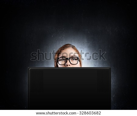 Young woman looking out above laptop monitor - stock photo