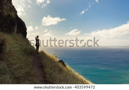 Young woman looking out at the beautiful ocean view.  - stock photo
