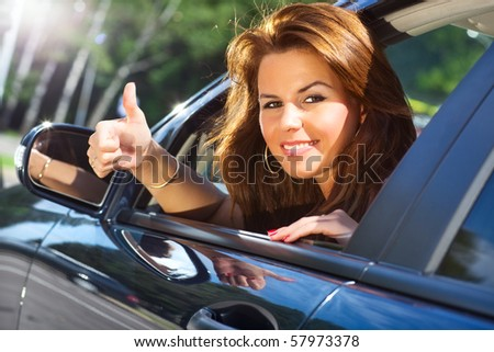 Young woman looking out of car and showing success handsign. - stock photo