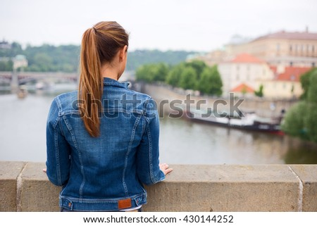 young woman looking out over the river enjoying the view. - stock photo