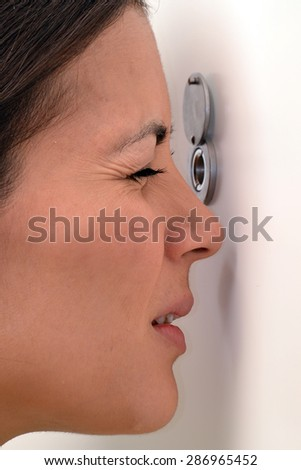 Young woman looking out through the peephole of her front door. - stock photo