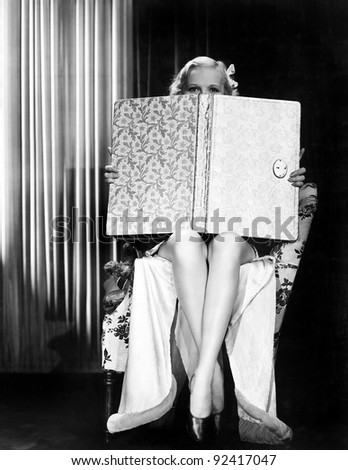Young woman looking over top of an oversized book - stock photo