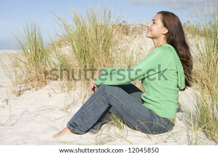 Young woman looking relaxed amongst dunes