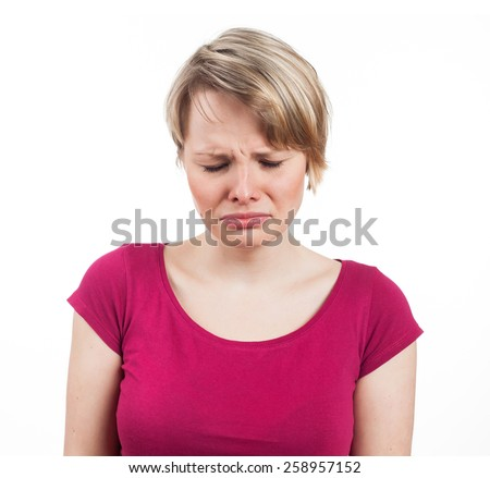 Young woman looking sad and about to cry, isolated on white - stock photo