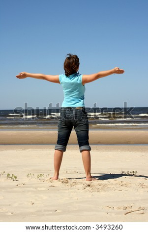 Young woman looking straight out to sea from beach(hands in sides)