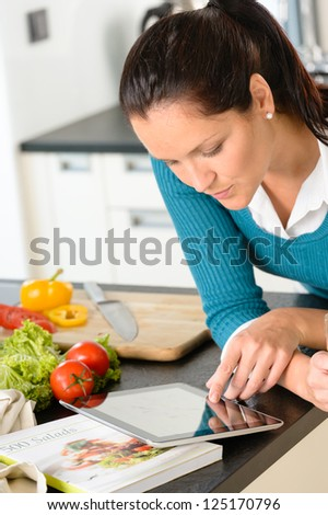 Young woman looking tablet recipe kitchen vegetables preparing food - stock photo