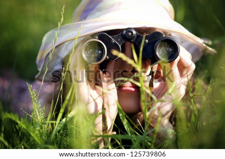 Young woman looking through binoculars in grass - stock photo