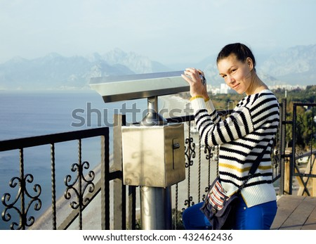 young woman looking through telescope at sea viewpoint in Atatur - stock photo