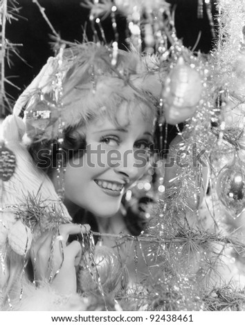 Young woman looking through the branches of a Christmas tree with ornaments - stock photo