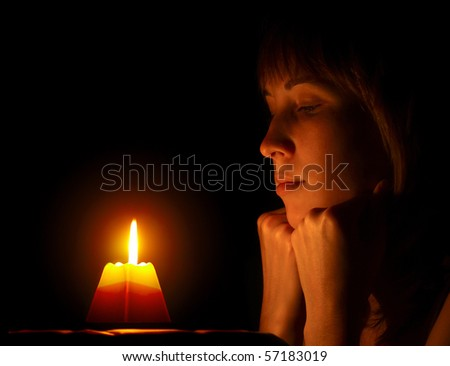 Young woman looking to a candle - stock photo