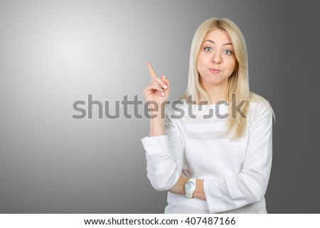 Young woman looking up and pointing at blank wall