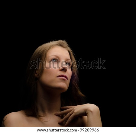 Young woman looking up and thinking - stock photo
