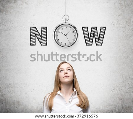 young woman looking up thinking about present opportunities and time. A pocket watch and the word 'now' over her head. Concrete background. Front view. Concept of present moment. - stock photo