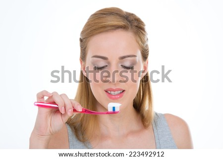 young woman looks her pink toothbrush and white toothpaste
