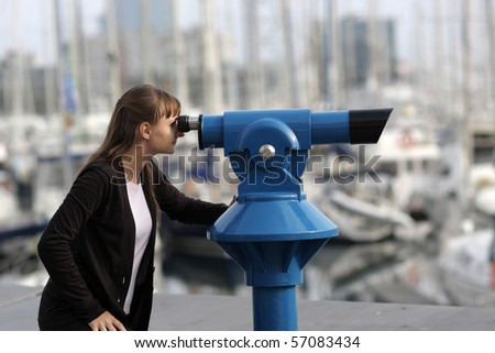 Young woman looks through telescope on city - stock photo