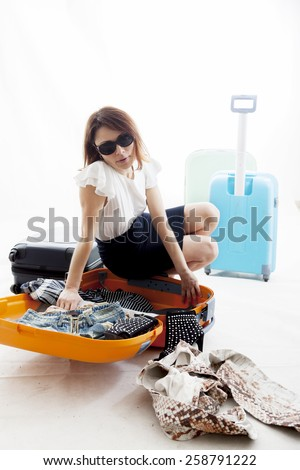 young woman lost the clothes from his suitcase - stock photo