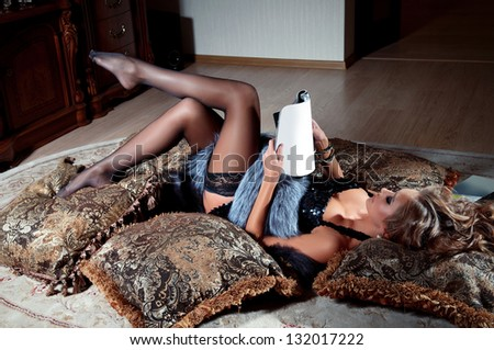 young woman lying and reading magazine indoor shot - stock photo