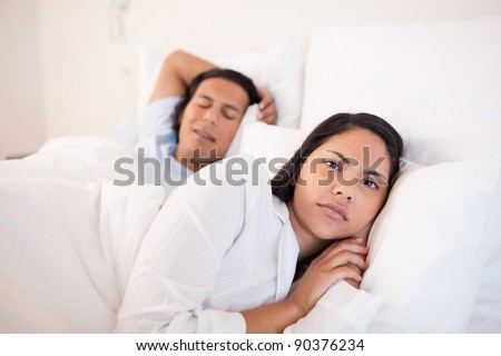 Young woman lying awake next to her sleeping boyfriend - stock photo