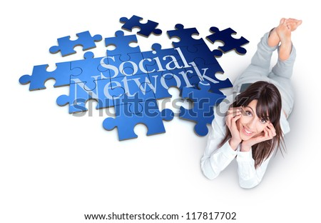 Young woman lying by a puzzle with the words Social Network - stock photo